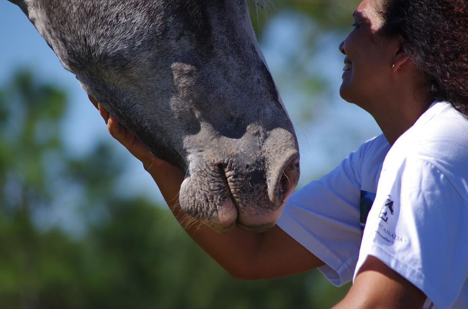 Marly sorrindo enquanto interage com cavalo