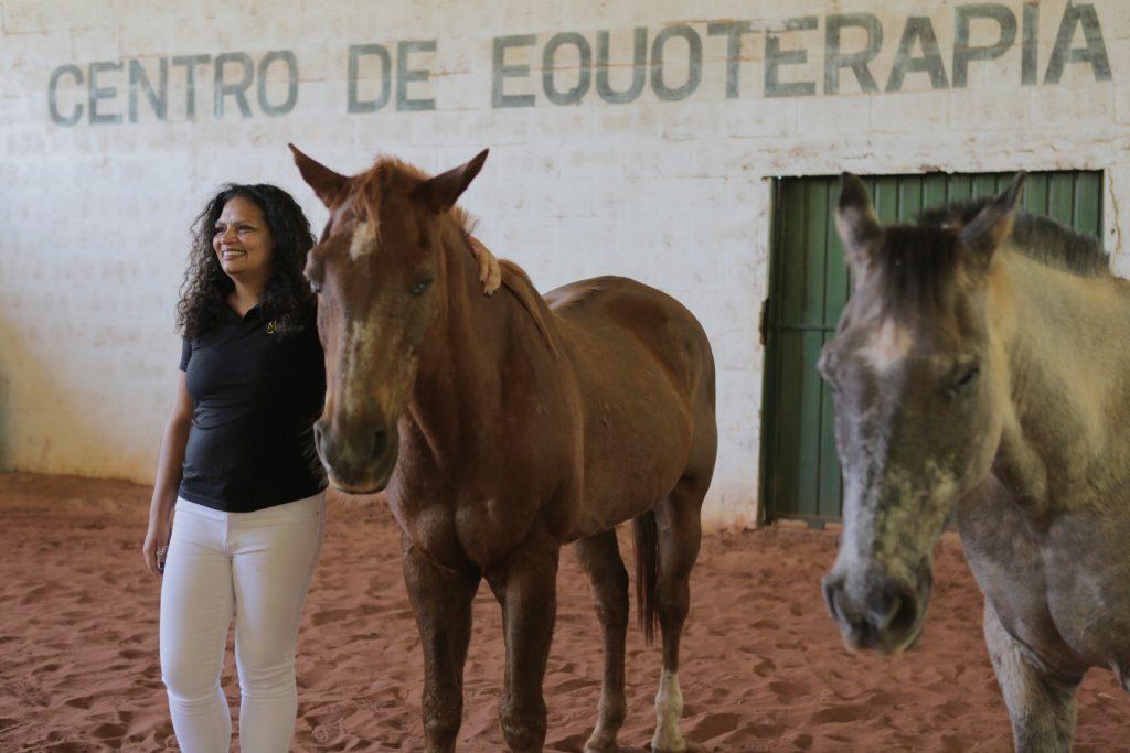 Marly abraçada à cavalo à direita