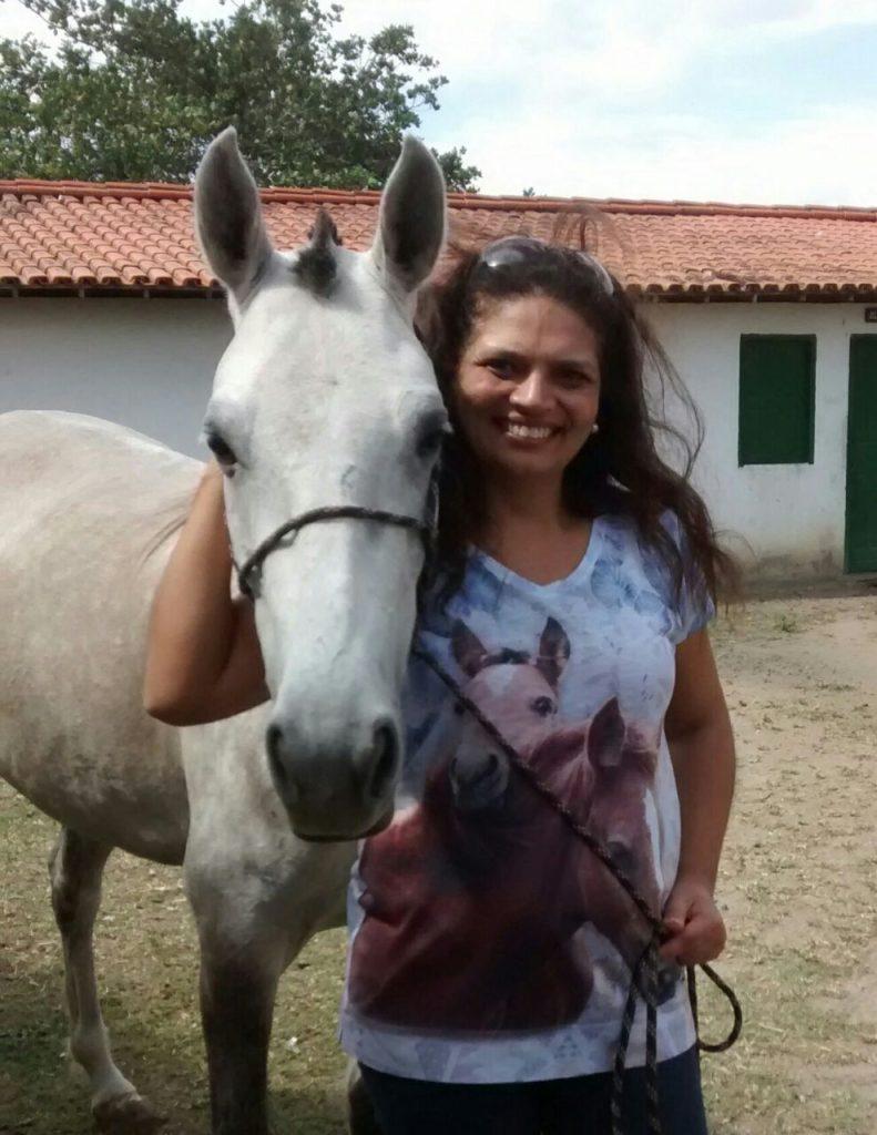 Marly sorrindo ao lado de cavalo branco