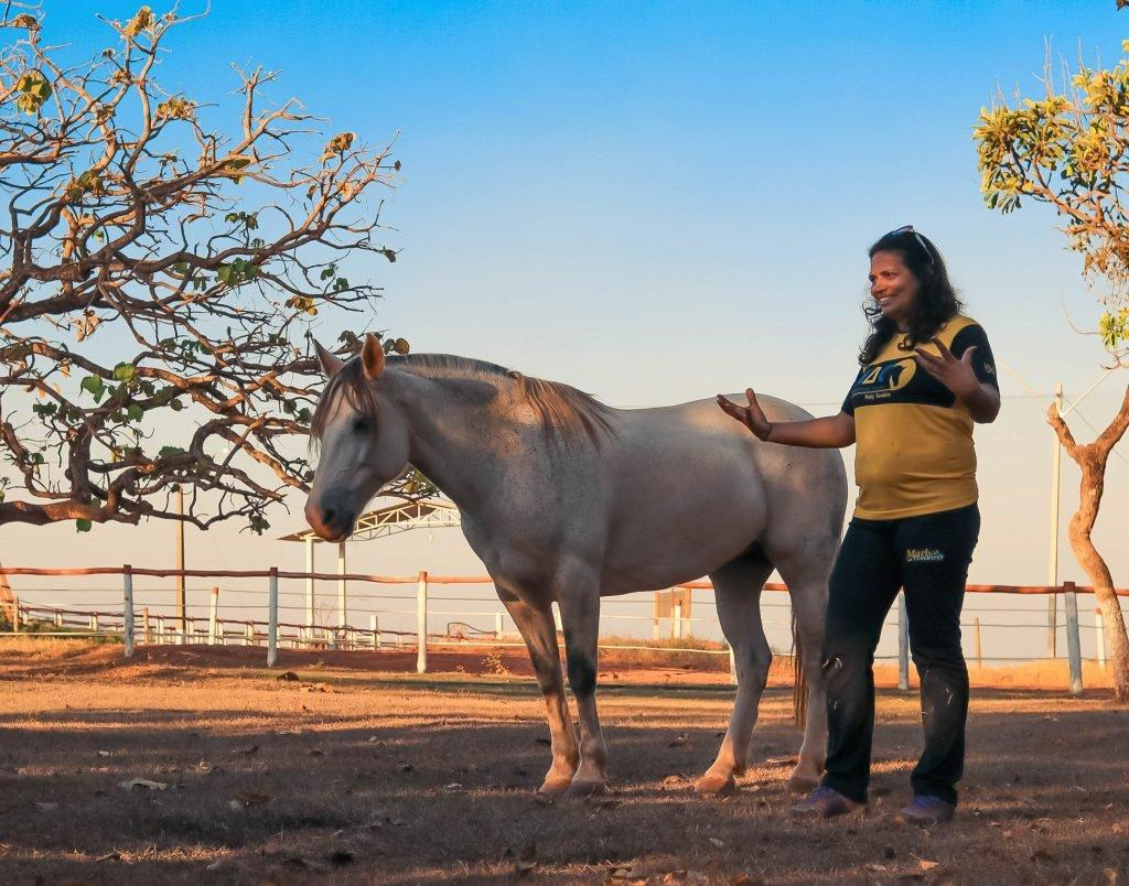 Marly discursando com entusiasmo ao lado do cavalo