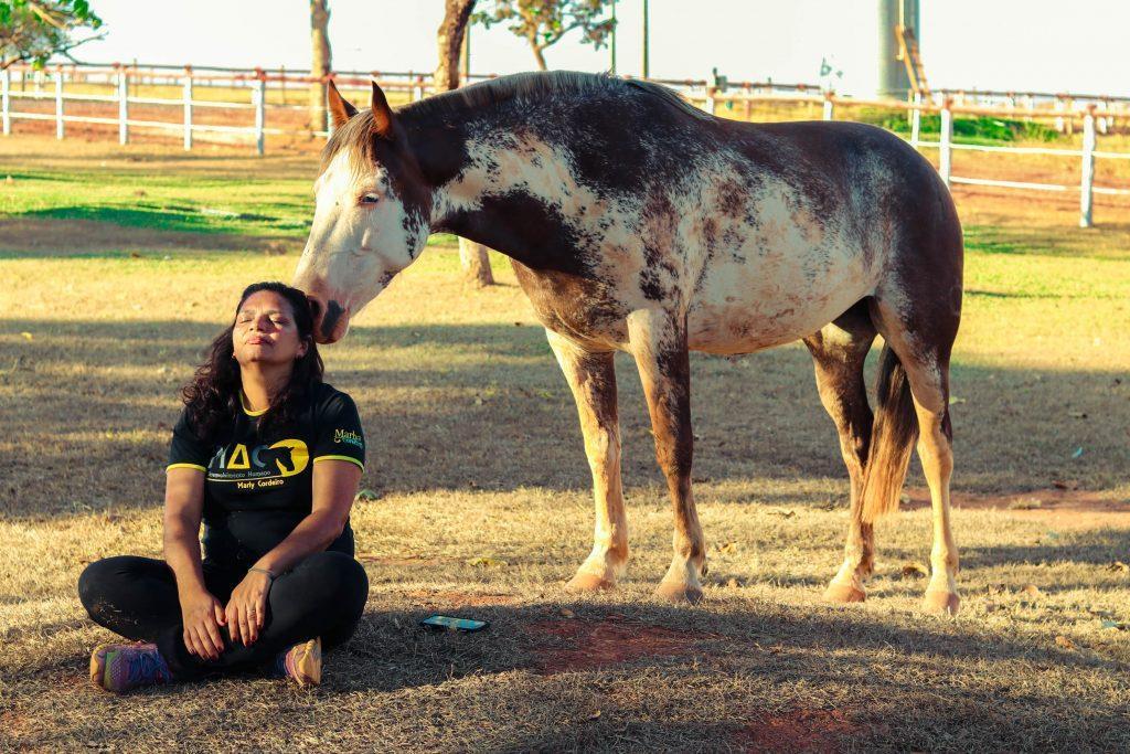Marly sentada no chão e sentindo a interação do cavalo