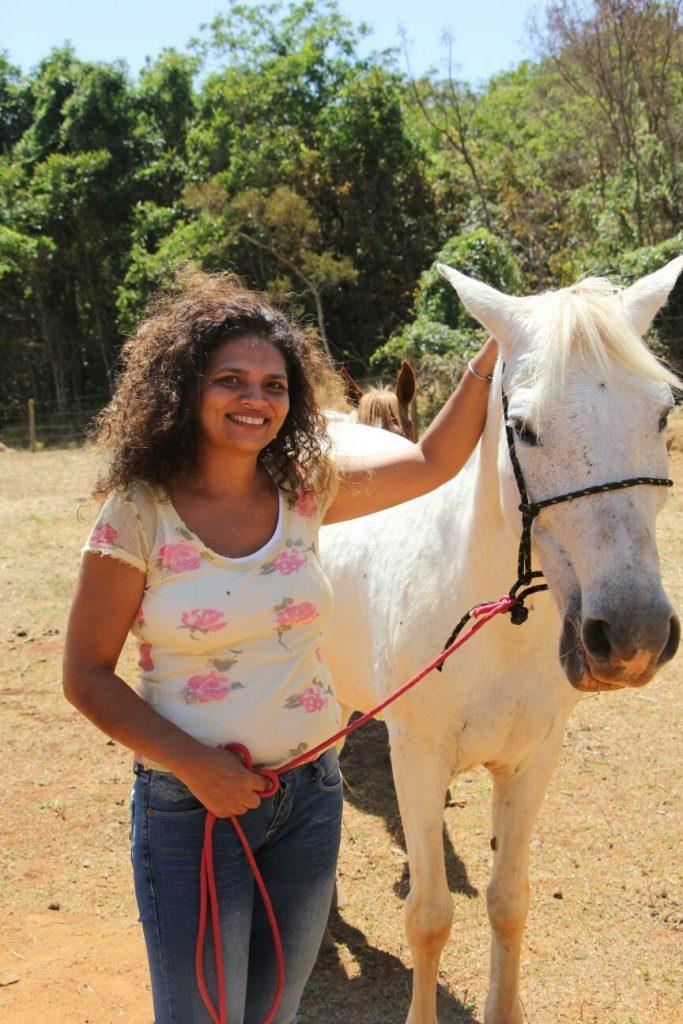 Marly sorrindo com cavalo branco à direita da foto